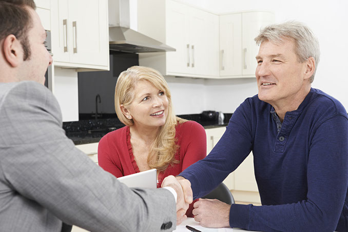 financial planning services 47650484 - mature couple shaking hands with financial advisor at home